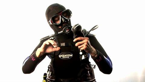 A scuba diver pretends to swim and check his depth Footage