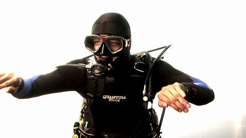 A scuba diver pretends to swim and check his depth Stock Video Footage