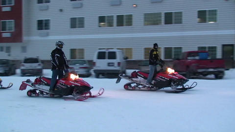 Snowmobiles ride through a town Stock Video Footage
