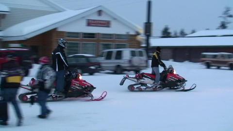 Snowmobiles ride through a town Stock Video Footage