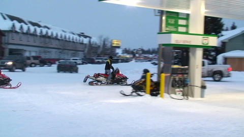 Snowmobiles ride through a town Footage