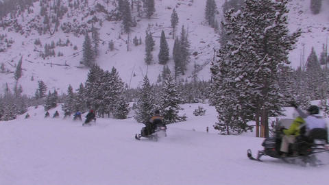 A long line of snowmobiles heads out across a snow Stock Video Footage