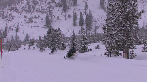 A long line of snowmobiles heads out across a snow Footage