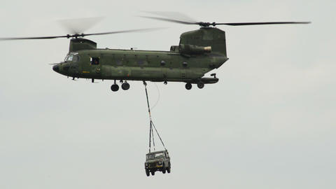 Chinook CH 47 helicopter carries a jeep on the hoo Stock Video Footage