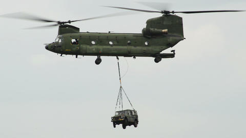 Chinook CH 47 helicopter carries a jeep on the hoo Footage