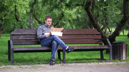 Man reads newspaper on bench in the park 1 Stock Video Footage