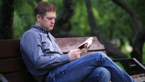 Man reads newspaper on bench in the park 2 Stock Video Footage