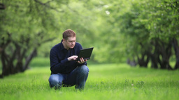 Man working with notebook in the park Stock Video Footage