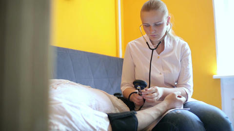 Doctor measures the blood pressure at home Stock Video Footage