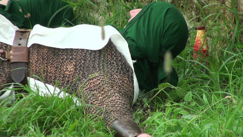 Warrior in chainmail lying on the grass Stock Video Footage