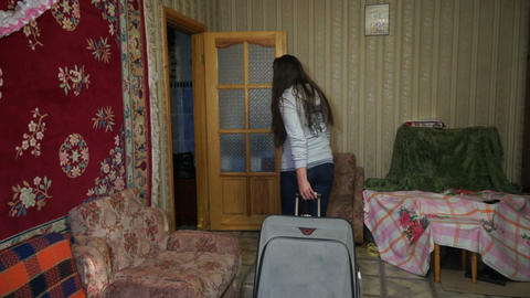 A woman with a suitcase out of the house Stock Video Footage