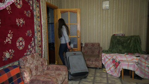 A woman with a suitcase out of the house Footage