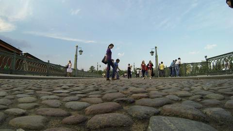 People walk across the bridge from pebbles Stock Video Footage
