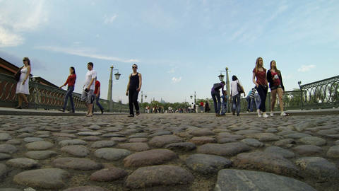 People walk across the bridge from pebbles Stock Video Footage