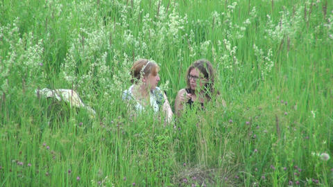 Two women sit in the grass Stock Video Footage
