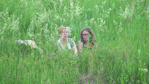 Two women sit in the grass Footage