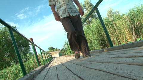 An elderly man goes on a wooden bridge Footage
