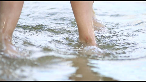 Legs of two young girls go on the water Stock Video Footage