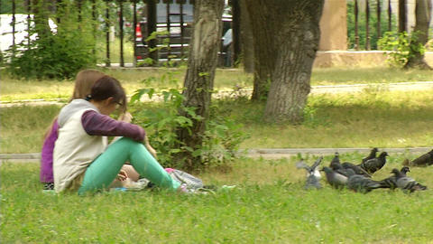 Girl friend feed the pigeons Stock Video Footage