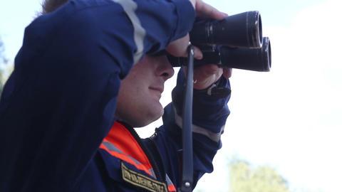 Rescuer looks in binoculars Stock Video Footage