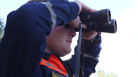 Rescuer looks in binoculars Footage
