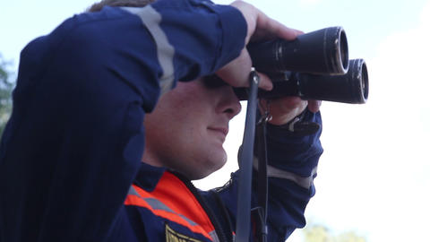 Rescuer looks in binoculars Stock Video Footage