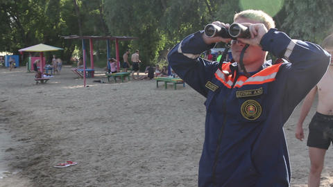Rescuer with binoculars on the beach Stock Video Footage