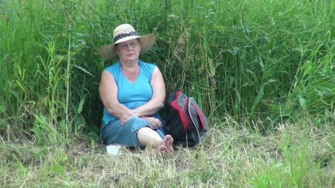 Elderly woman sitting in the grass Stock Video Footage