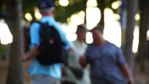 People Walking in a park de-focused right to left Stock Video Footage