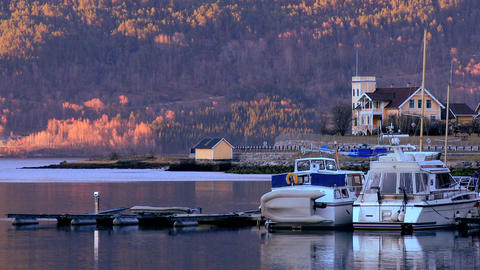 Sunset over leisure cruisers on a fjord beside a small... Stock Video Footage