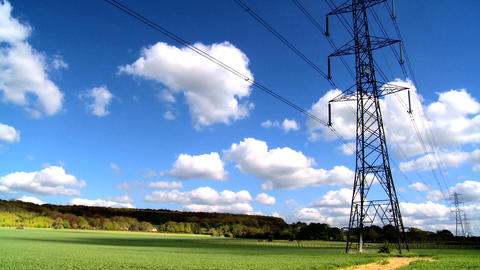 Time-lapse clouds over a field with electricity pylons Footage