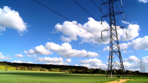 Time-lapse clouds over a field with electricity pylons Stock Video Footage