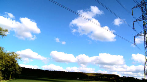 Electricity pylon in a field with blue sky & white clouds Footage