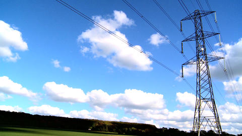 Electricity pylon in a field with blue sky & white clouds Stock Video Footage