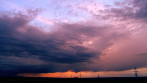 Time-lapse storm clouds at sunset over a horizon full of elecrticity pylons Footage