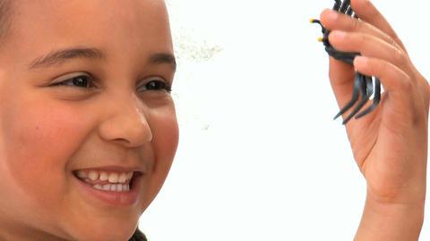 Cute african american schoolgirl examines a plastic spider Stock Video Footage