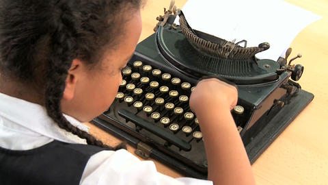 Cute african american schoolgirl using an old fashioned typewriter Footage
