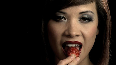 Sensuous western oriental girl slowly biting into a strawberry Footage