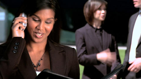 Young city business woman,with colleagues,talking on mobile(cell)phone Footage