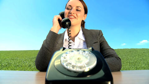 Concept shot of young businesswoman in city clothes using old-fashioned telephone Footage