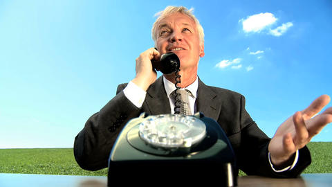 Concept shot of business man in city clothes using old-fashioned telephone in environmental office Footage