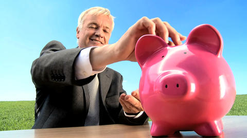 Businessman using money pig for green investment in an environmental future Footage