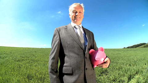 Businessman with money pig for green investment in an... Stock Video Footage