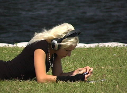 Beautiful Blonde with Headphones Outdoors Footage