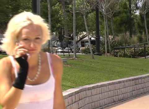 Beautiful Blonde Rollerblading Outdoors with Cell Phone (2) Stock Video Footage