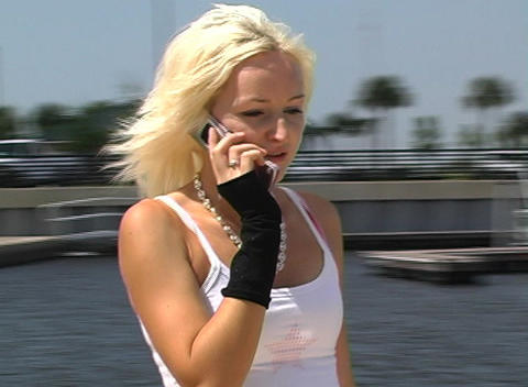 Beautiful Blonde Rollerblading Outdoors with Cell Phone (2) Footage