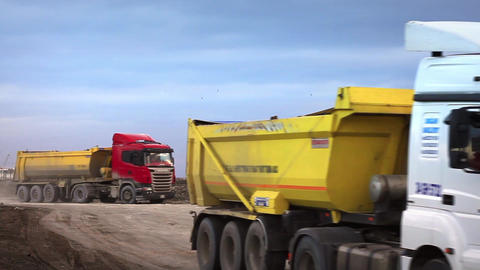 Dump trucks running at construction site Stock Video Footage