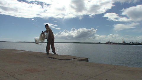 Cienfuegos Harber fisherman throws his net into wa Stock Video Footage