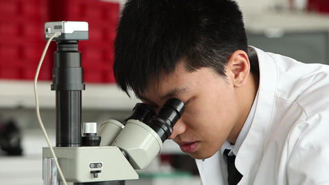 Young asian male scientist looking into microscope Stock Video Footage