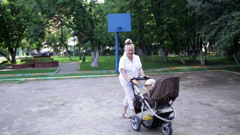 Grandmother walks with her grandson in the yard Stock Video Footage